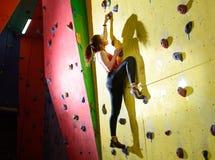 Jonge Actieve Vrouw Bouldering op Kleurrijke Kunstmatige Rots in het Beklimmen van Gymnastiek Extreme Sport en Binnen het Beklimm royalty-vrije stock afbeeldingen