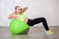 Jonge actieve vrouw die pilates oefeningen in geschiktheidsstudio doen Stock Foto's