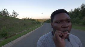 Jonge Afrikaans-Amerikaanse mens die onderaan de lege weg en de rokende sigaret bij zonsondergang lopen stock footage