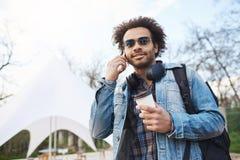 Jonge Afrikaans-Amerikaanse reiziger met de holdingskoffie van het afrokapsel terwijl het lopen en het spreken op smartphone, het royalty-vrije stock afbeelding