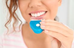 Jonge Afrikaans-Amerikaanse vrouw die tanden gebruiken die apparaat op lichte achtergrond witten royalty-vrije stock foto