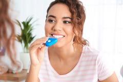 Jonge Afrikaans-Amerikaanse vrouw die tanden gebruiken die apparaat witten stock foto
