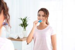 Jonge Afrikaans-Amerikaanse vrouw die tanden gebruiken die apparaat witten royalty-vrije stock foto