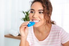 Jonge Afrikaans-Amerikaanse vrouw die tanden gebruiken die apparaat witten royalty-vrije stock afbeeldingen