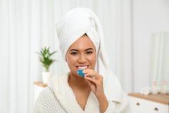 Jonge Afrikaans-Amerikaanse vrouw die tanden gebruiken die apparaat witten stock afbeeldingen