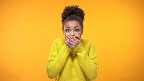 Jonge Afrikaans-Amerikaanse vrouwen sluitende mond met handen, die geheim, roddel houden royalty-vrije stock afbeeldingen