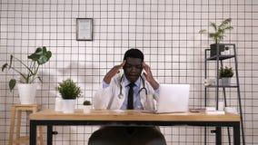 Jonge Afrikaanse Amerikaanse arts die aan wanhopig en beklemtoonde hoofdpijn lijden omdat pijn en migraine Handen op hoofd stock footage