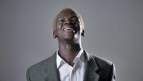 Jonge Afrikaanse Amerikaanse blonde mens in kostuum die die en camera glimlachen bekijken, op grijze achtergrond wordt geïsoleerd stock videobeelden
