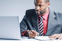 Jonge Afrikaanse Amerikaanse Laptop van Zakenmanbeing sneaky on Stock Fotografie
