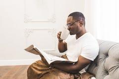 Jonge Afrikaanse Amerikaanse mens, thuis omvat met een algemene lezing een krant stock foto's