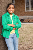 Jonge Afrikaanse Amerikaanse tiener status buiten en het glimlachen Stock Fotografie