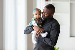 Jonge Afrikaanse Amerikaanse vaderholding met haar babymeisje Royalty-vrije Stock Afbeeldingen