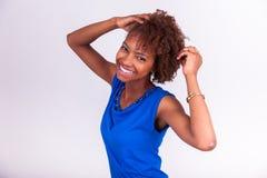 Jonge Afrikaanse Amerikaanse vrouw die haar kroes- afrohaar houden - Blac Royalty-vrije Stock Fotografie