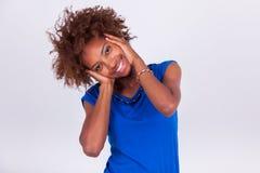 Jonge Afrikaanse Amerikaanse vrouw die haar kroes- afrohaar houden - Blac Stock Afbeeldingen