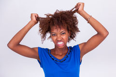 Jonge Afrikaanse Amerikaanse vrouw die haar kroes- afrohaar houden - Blac royalty-vrije stock foto's