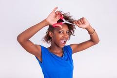 Jonge Afrikaanse Amerikaanse vrouw die haar kroes- afrohaar met s snijden royalty-vrije stock foto