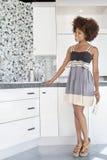 Jonge Afrikaanse Amerikaanse vrouw die ontworpen muur in nieuw huiskeuken bewonderen Stock Foto's