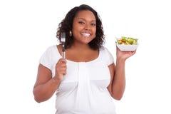 Jonge Afrikaanse Amerikaanse vrouw die salade eet Stock Afbeeldingen