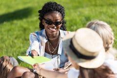 Jonge Afrikaanse Amerikaanse vrouw in zonnebril die handboek geven aan klasgenoten terwijl het zitten op gras in park royalty-vrije stock afbeelding