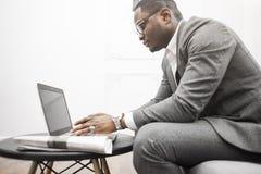 Jonge Afrikaanse Amerikaanse zakenman in een grijs kostuum die achter laptop werken royalty-vrije stock afbeeldingen