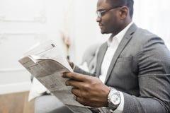 Jonge Afrikaanse Amerikaanse zakenman in een grijs kostuum die een krant lezen terwijl het zitten op een bank stock fotografie