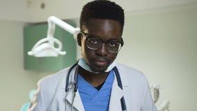 Jonge Afrikaanse arts die glazen in het het ziekenhuisbureau dragen stock video
