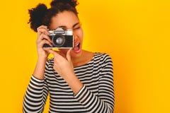 Jonge Afrikaanse die vrouw op gele de tienerstijl wordt geïsoleerd die van de muurstudio beeldenclose-up nemen stock afbeeldingen