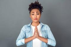 Jonge Afrikaanse die vrouw op grijs de levensstijl van de muurstudio toevallig dagelijks het bidden gebaar wordt geïsoleerd stock afbeelding
