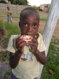 Jonge Afrikaanse jongen die granaatappelfruit eten Stock Foto