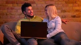 Jonge Afrikaanse kerel en Kaukasische meisjeszitting op bank met laptop en het koesteren zijnd blij thuis en ontspannen stock videobeelden
