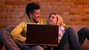 Jonge Afrikaanse kerel en Kaukasische meisjeszitting op bank met laptop en vreugdevol thuis het spreken met elkaar stock videobeelden