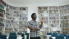 Jonge Afrikaanse mannelijke student die in de moderne bibliotheek dansen terwijl het luisteren muziek in de hoofdtelefoon stock video