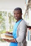 Jonge Afrikaanse mens die in bibliotheek glimlacht royalty-vrije stock fotografie