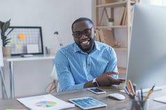 Jonge Afrikaanse mens die in de bureauzaken werken Stock Afbeelding