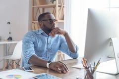 Jonge Afrikaanse mens die in de bureauzaken werken Stock Foto