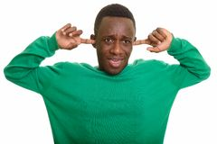 Jonge Afrikaanse mens die oren behandelen met vingers stock afbeelding