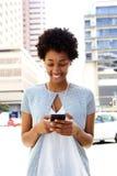 Jonge Afrikaanse vrouw die aan muziek op de mobiele telefoon luisteren Stock Afbeelding