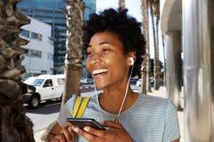 Jonge Afrikaanse vrouw die aan muziek op mobiele telefoon luisteren Royalty-vrije Stock Afbeeldingen