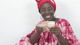 Jonge Afrikaanse vrouw die en haar geld zitten tellen stock video