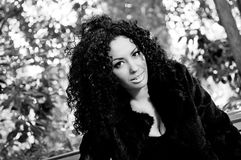 Jonge Afrikaanse vrouw die op bank in park situeert Stock Afbeeldingen