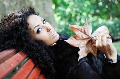 Jonge Afrikaanse vrouw die op bank in park situeert Royalty-vrije Stock Foto