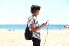 Jonge Afrikaanse vrouw status buiten en het luisteren aan muziek van slimme telefoon Royalty-vrije Stock Afbeelding