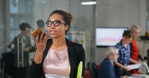 Jonge Afrikaanse vrouwelijke secretaresse die audiobericht registreren stock footage