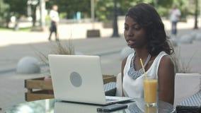 Jonge Afrikaanse vrouwenzitting alleen in een koffie die een videoconferance op laptop hebben stock video