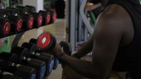 Jonge Afro-Amerikaanse atleet die de krulzitting van de bicepsendomoor in gymnastiek doen stock videobeelden