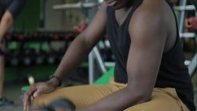 Jonge Afro-Amerikaanse mens die de krul doen van de bicepsendomoor terwijl het zitten in gymnastiek stock video