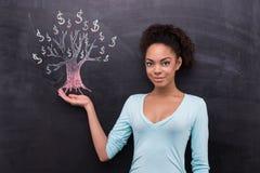 Jonge Afro-Amerikaanse vrouw en dollar geschilderde boom Stock Afbeelding