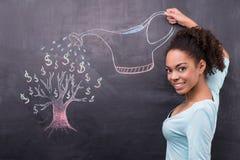 Jonge Afro-Amerikaanse vrouw het water geven dollarboom Stock Afbeelding