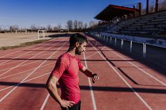Jonge agentmens die slim horloge in de atletieksteeg controleren Sporten in openlucht royalty-vrije stock afbeelding