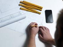 Jonge ambitieuze architect die de blauwdruk van een nieuwe hous voorstellen Royalty-vrije Stock Afbeelding